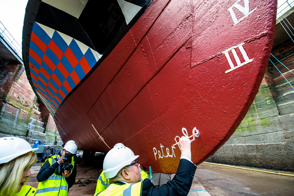 Sir Peter Blake painting his signature on the hull of the Dazzle Ferry